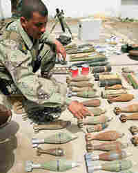 Iraqi army soldiers inspect a cache of weapons found during a raid in the Iraqi city of Basra.