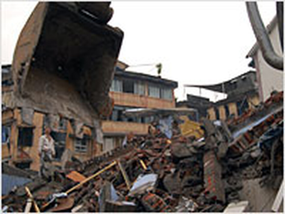 Wang Wei stands atop the rubble of his family's  apartment building in Dujiangyan, China.