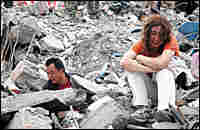 A Chinese couple in Mianyang city search for their son in the ruins of Monday's earthquake
