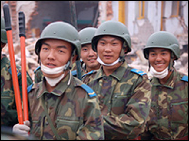 After freeing a man who had been trapped since Monday's quake, soldiers march off proudly.