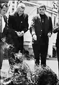 Fathers Daniel and Phillip Berrigan burning draft records.