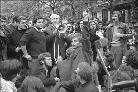 Student leader Daniel Cohn-Bendit raises his arm for silence to allow poet Louis Aragon to talk to students on a megaphone. [Photo by Serge Hambourg/via NPR]