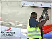 An airline worker removes a fuel line from a Southwest Airlines plane.