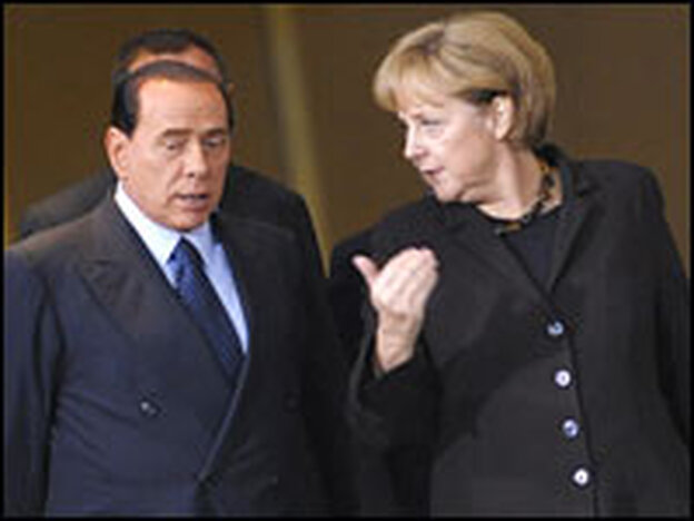 Italian Prime Minister Silvio Berlusconi (left) and German Chancellor Angela Merkel make their way to a press conference in Berlin on Monday.