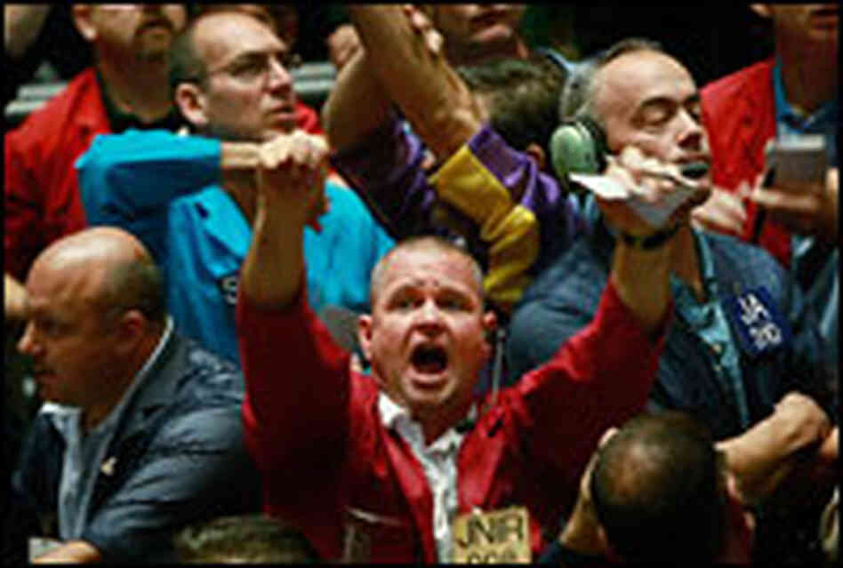 Traders in the S&P 500 stock index futures pit at the Chicago Board of Trade signal offers on Friday