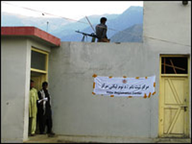A policeman stands guard on the rooftop of a voter registration center in Shigal district of volatile Kunar province in eastern Afghanistan.