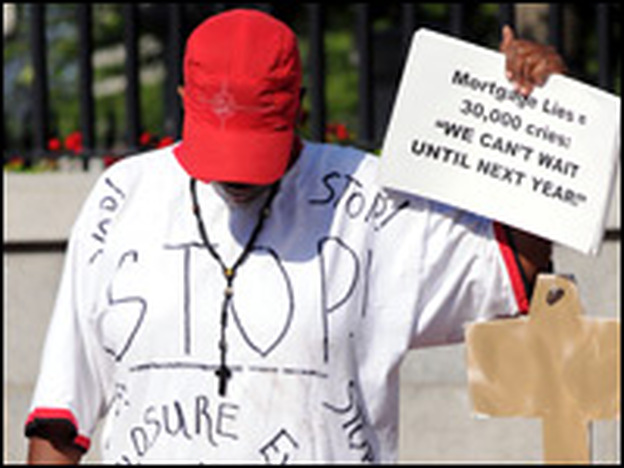 Deborah Williams holds a sign and a homemade key while wearing a shirt in memory of Carlene Balderrama, a Massachusetts woman who committed suicide before foreclosure of her home in July 2008 in Boston.