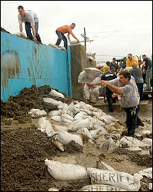 Prisoners and others work on stopping the flooding underneath a floodgate.