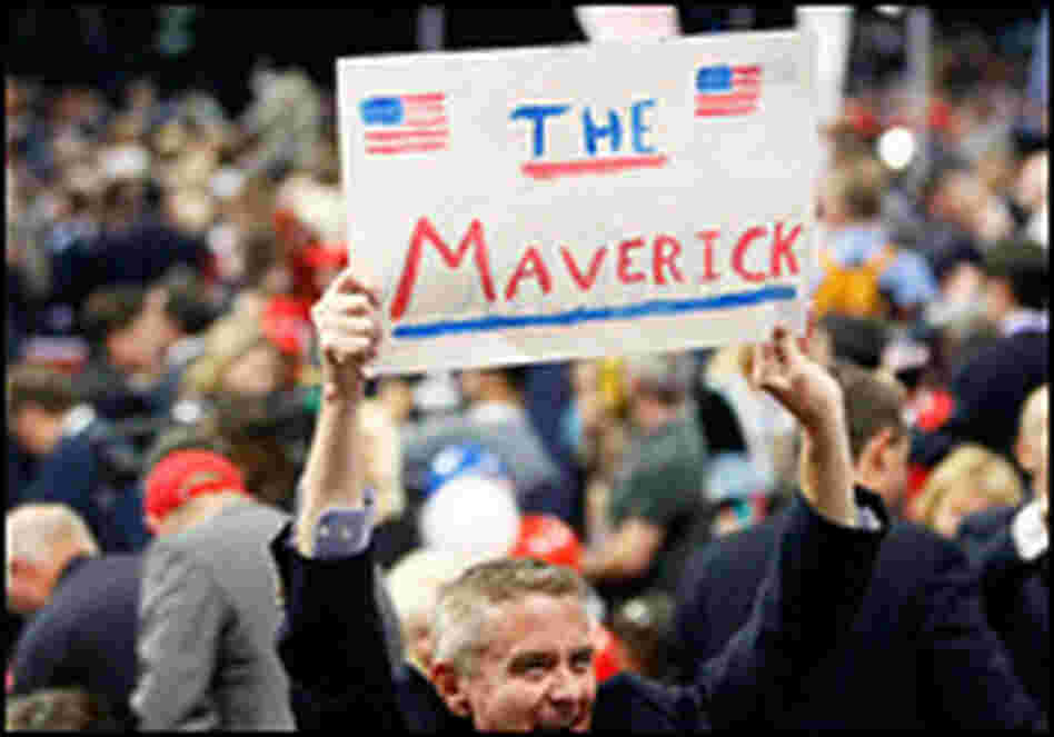 "A man at the Republican National Convention holds up a sign reading ""The Maverick."""