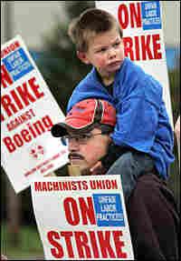 Boeing machinist Scott Green, with his son Joshua, 3, walks the picket line on Saturday.