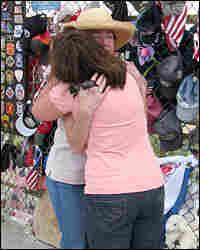 Deborah Borza (left) hugs a visitor at the temporary memorial for Flight 93 in Shanksville, Pa.