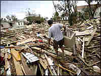 Galveston, Texas, resident Bill Higgins walks over storm debris, searching for his neighbor's pets