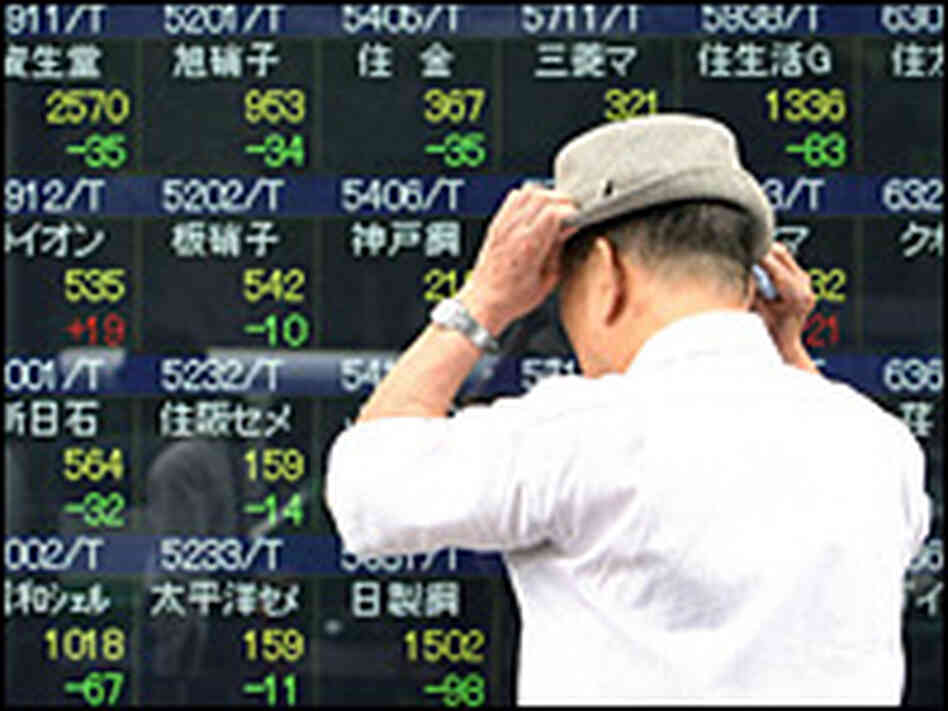 A man looks at an electronic display board showing falling share prices in Tokyo on Tuesday.