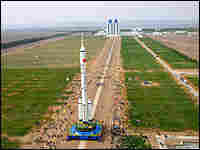 Workers move a rocket carrying China's manned spacecraft from the assembly plant to a launch pad.