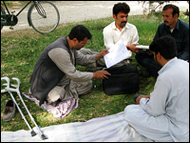 Four of the employees of the Disabled Cycle Messenger Services gather at a Kabul park to organize their deliveries for the day.