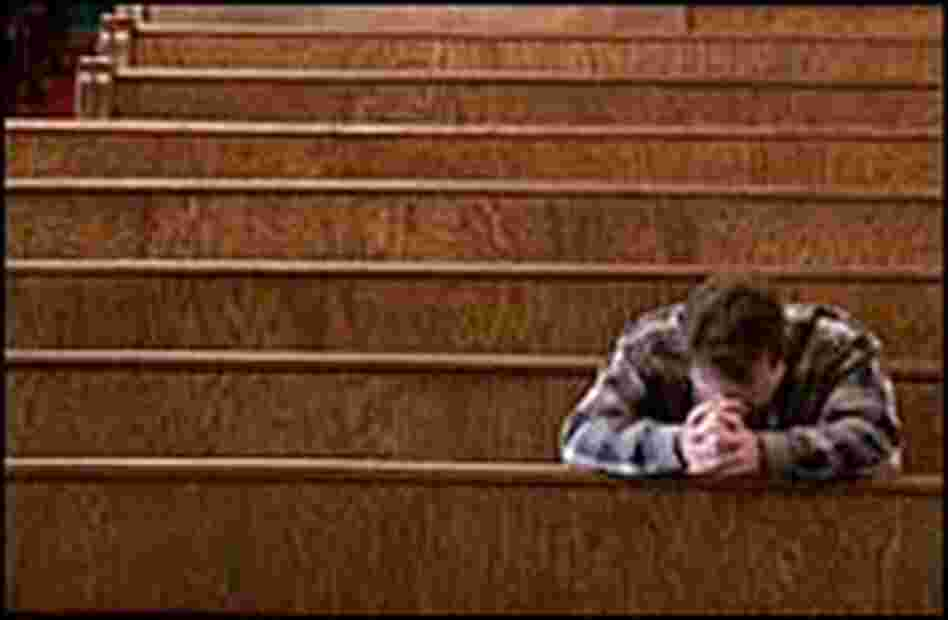 A man prays in a church.