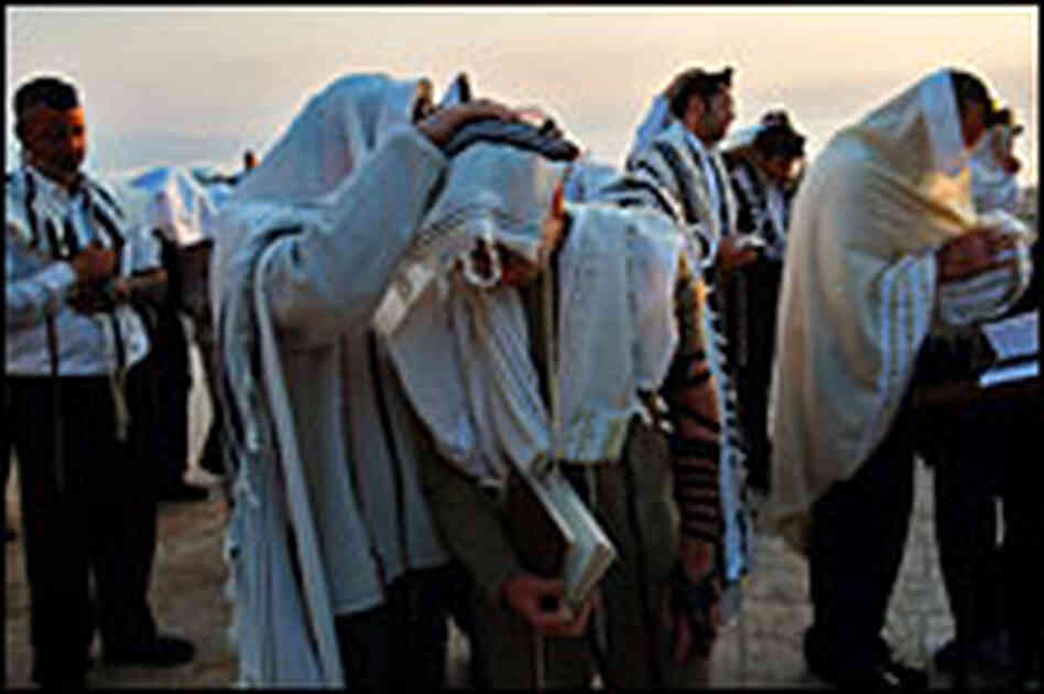 Religious Jews cover themselves and their sons to receive the priestly blessing in Israel Wednesday.