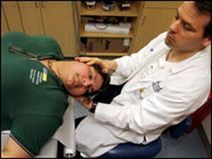 Audiologist Saul Strieb moves Tiwari through  a series of head and body positions to clear the otoconia (ear rocks or pebbles) out of the semicircular canals.