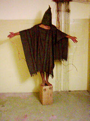 Unidentified detainee stands on a box with a bag on his head and wires attached to him at Abu Ghraib
