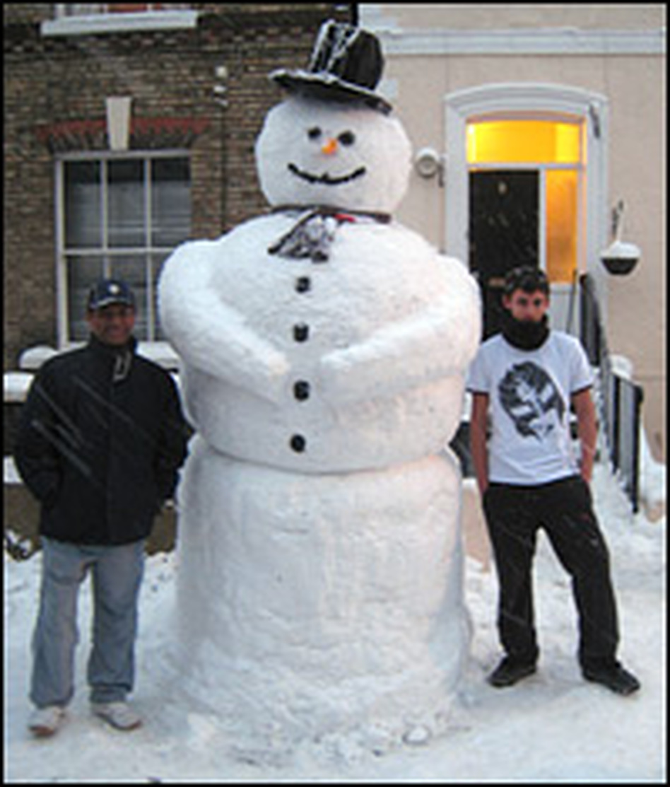 Hussein Nawal and his son, Dean, stand beside the snowman they built in Crystal Palace, South London, on Feb. 2.