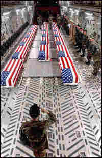 Flag-draped coffins of U.S. casualties from Iraq are unloaded from a plane by a military honor guard