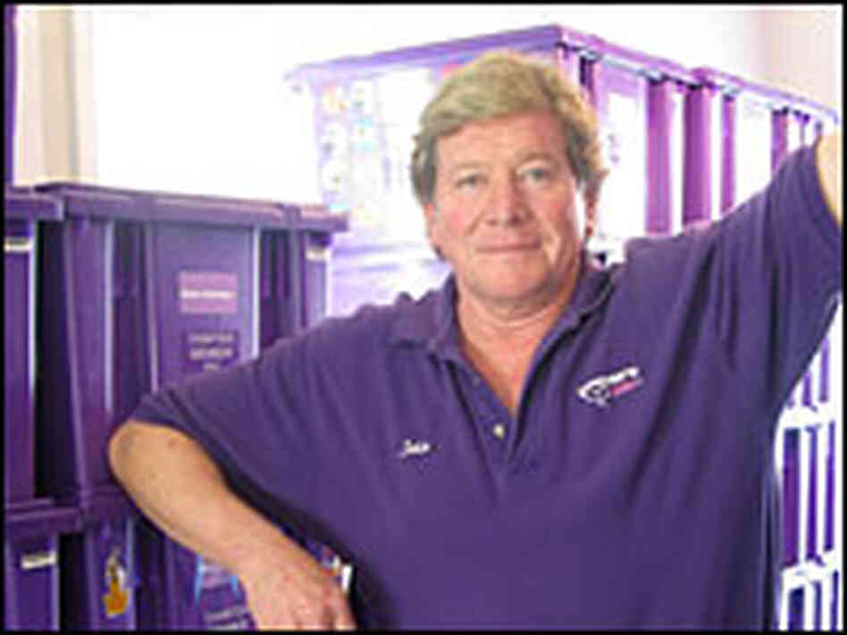 John Van Meter, founder of Owner's Locker, stand in a storage room surrounded by purple containers