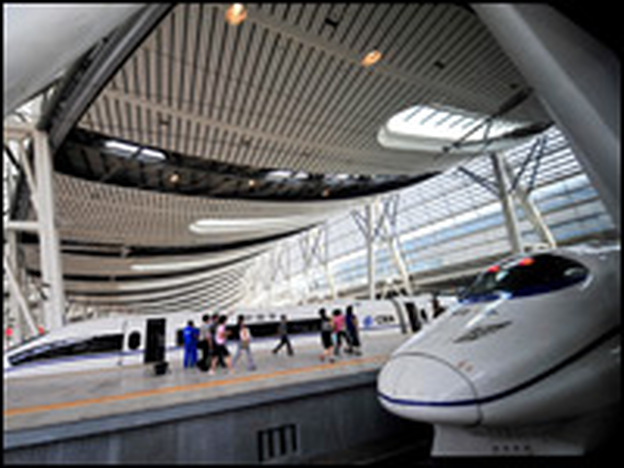 Visitors walk past bullet trains at a station in Beijing. China is one of many countries that makes use of high-speed rail.