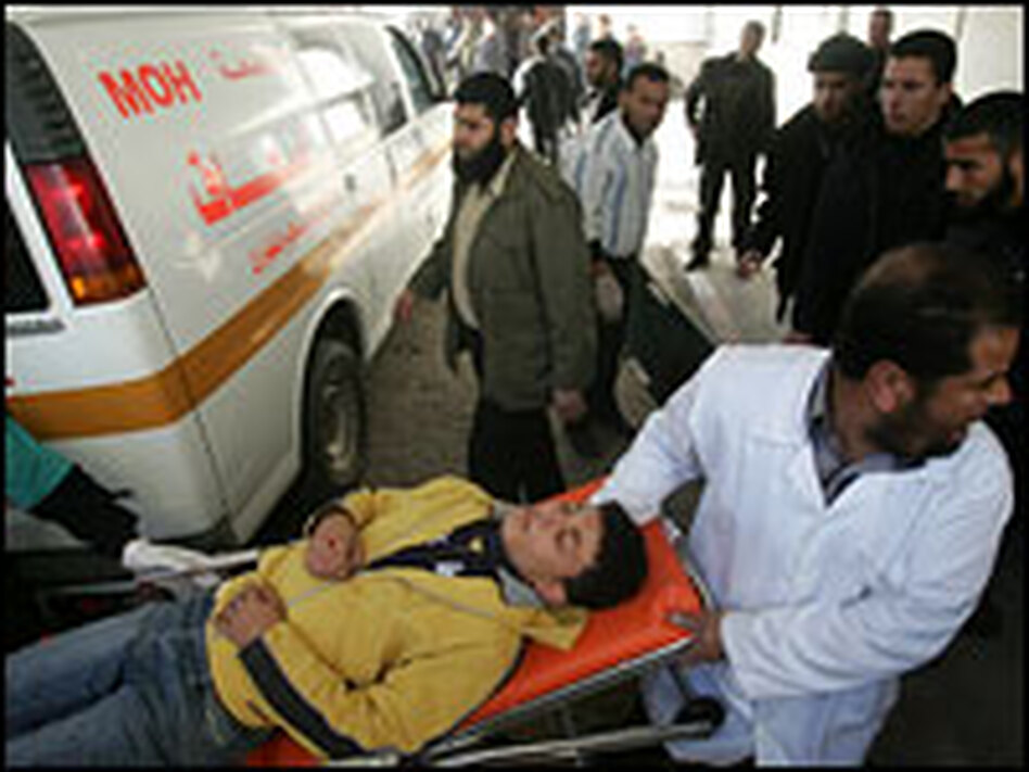 A wounded Palestinian boy is carried by stretcher upon arriving at Shifa Hospital.
