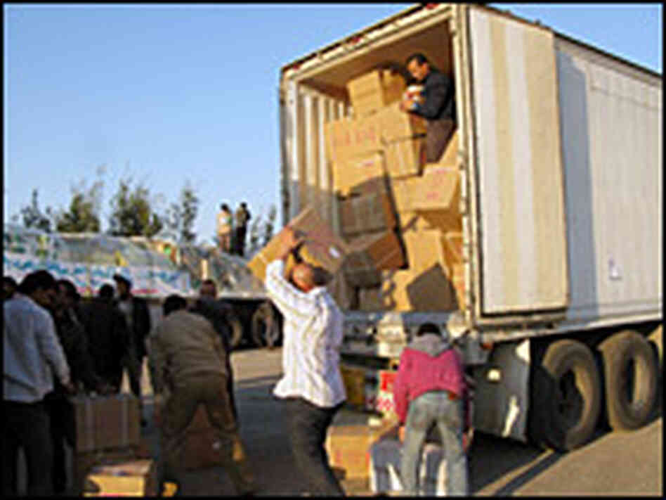Volunteers at the Egypt-Gaza border at Rafah transfer medical supplies from an Egyptian truck to a P