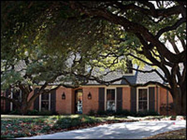 Trees shade the front of a house in the Preston Hollow neighborhood Dec. 5 in Dallas. The Bushes' new home reportedly spans about 8,500 square feet.