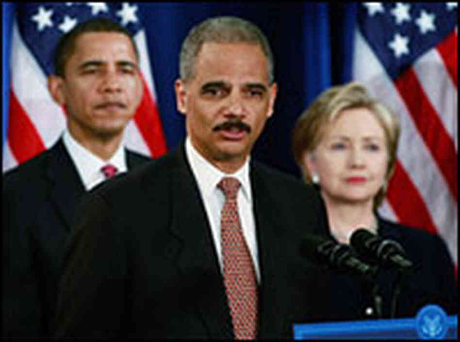 Attorney general nominee Eric Holder speaks as Barack Obama and Hillary Clinton stand by Dec. 1