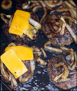 Burgers topped with griddled onions and sliced cheese