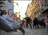 Runners lead fighting bulls around a corner