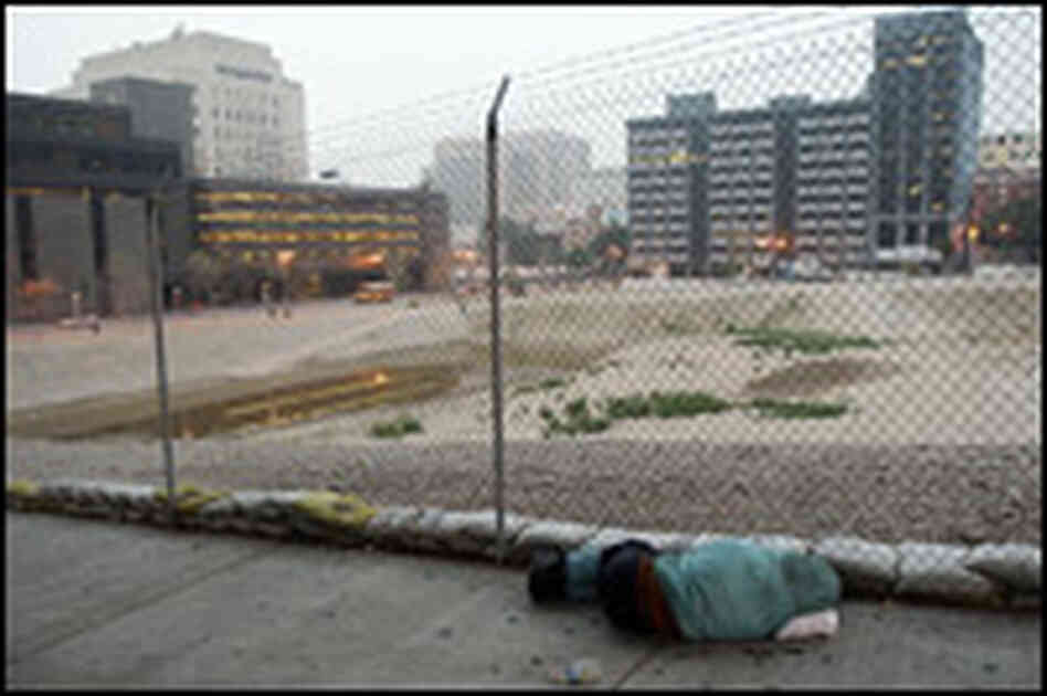 A homeless man sleeps on the sidewalk next to a  lot in downtown LA