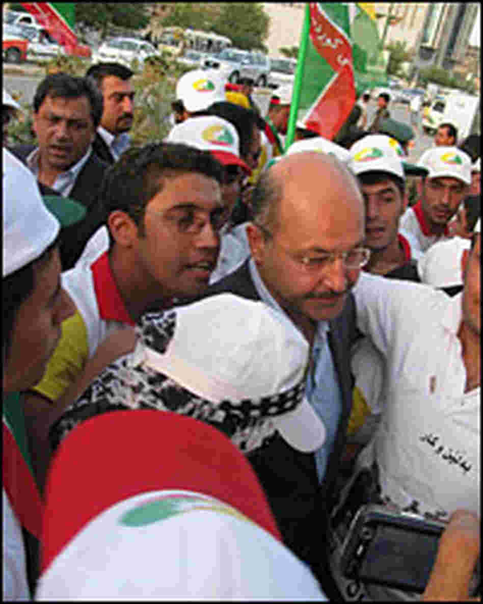 Barham Salih is surrounded by supporters at a rally in Sulimaniya