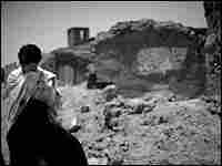 A villager in Azizabad stands near the destroyed homes.