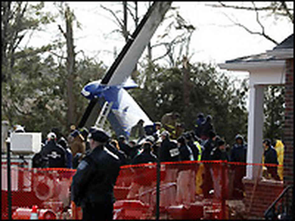 Workers and investigators clear debris from the scene of the plane crash of Continental Flight 3407.