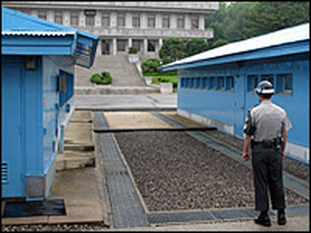 A South Korean soldier in the Joint Security Area in Panmunjom. The concrete strip at the end of the gravel at center marks the border. In the background is a North Korean building.