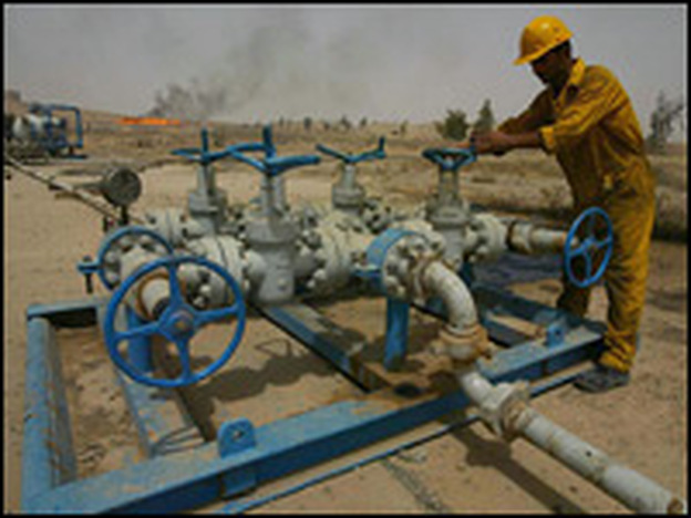 An Iraqi worker checks the valves at the Kirkuk oil field. Tuesday, the government of Iraq opens bids from oil companies interested in helping the country increase its oil production.