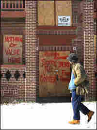 A man walks past a boarded-up building in Cleveland.