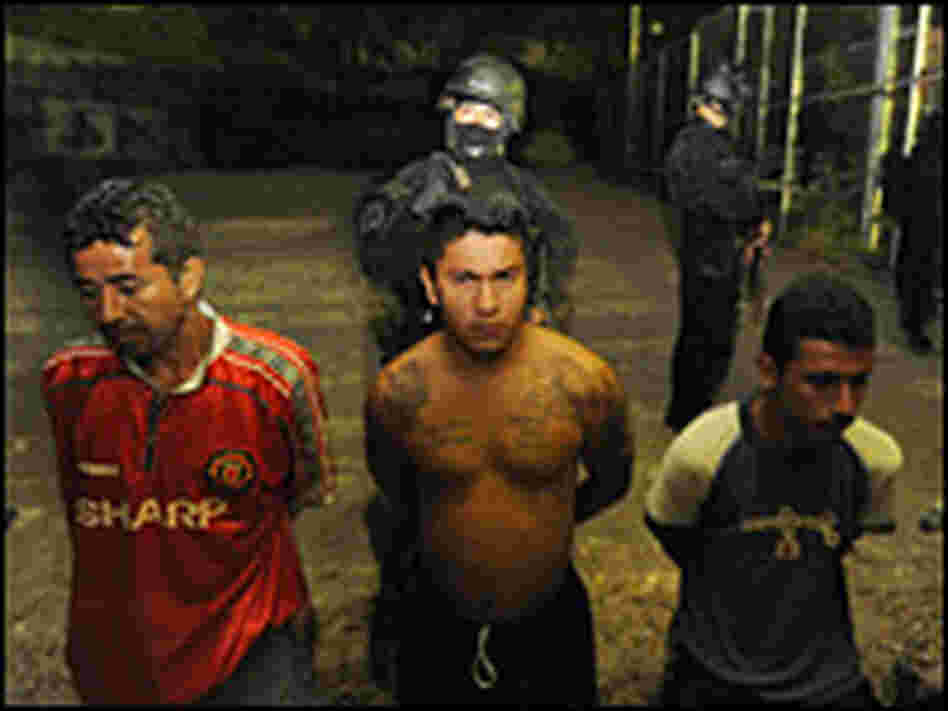 Members of El Salvador's National Civil Police guard suspected members of the notorious gang 18