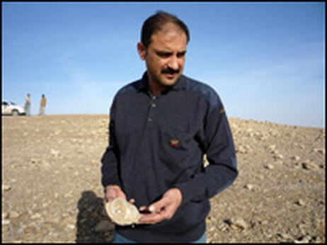 Dr. Yousif Jasir Muhammed picks up a shard of pottery at a newly discovered Roman-era site