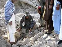 Afghan villagers sift through the rubble of destroyed houses Tuesday.