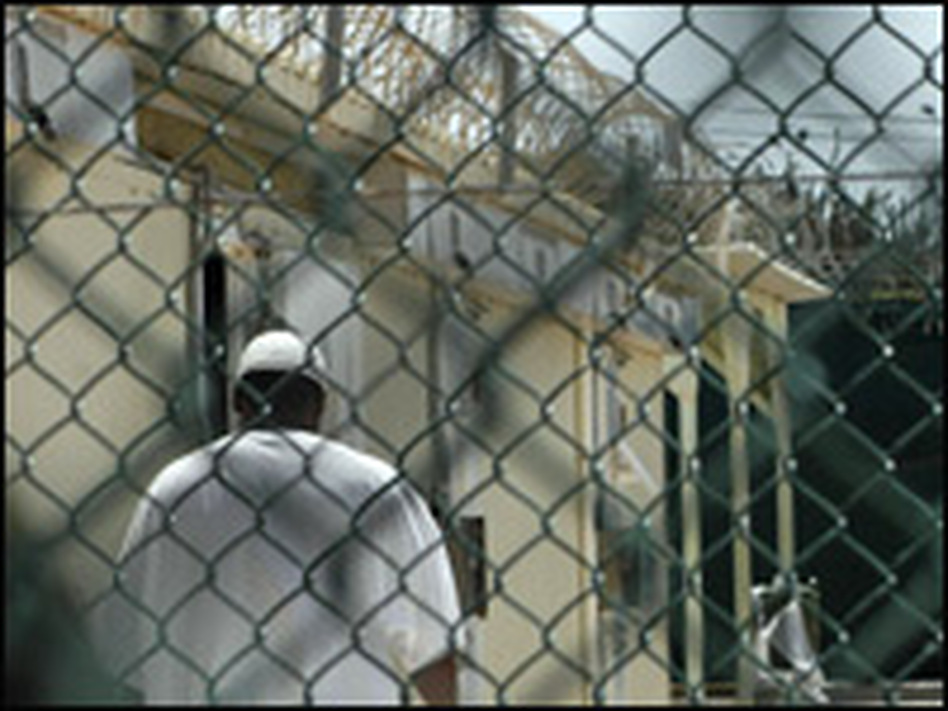 In this 2008 image reviewed by the U.S. military, a detainee is visible through fencing around a cell block at the U.S. naval base in Guantanamo Bay, Cuba.