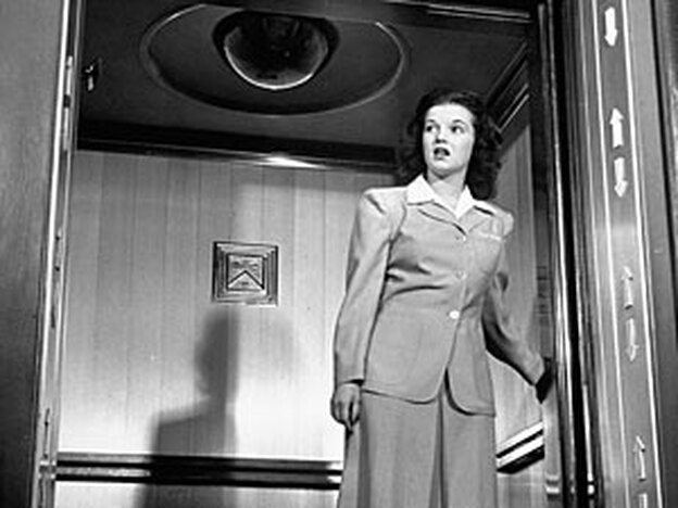 An elevator girl from Marshall Fields department store demonstrates correct posture in 1947 with the help of some Muzak.