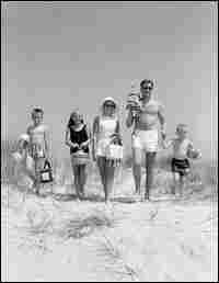 An American family of five walks toward the beach in bathing suits, circa 1960s.