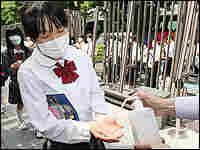 Middle school students wearing facemasks get their hands disinfected in Tokyo.