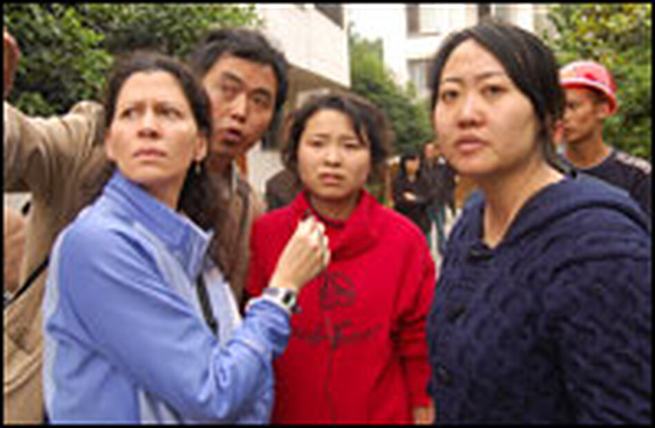 Melissa Block (left) stands with Wang Dan (far right) last May as they assess the scene two days after the earthquake. Wang Dan lost her parents and her nephew when an apartment building collapsed on them.