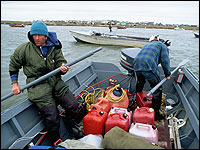 Two men in a small motorboat loaded with containers float in the Bering Strait off Shishmaref, Alaska.