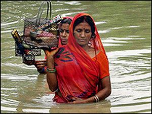Bangladeshi women make their way through flood water at Dhakuria in Sirajgonj district.